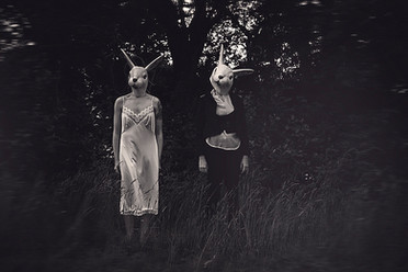 This is a black and white landscape image of two figures stood in tall grass in front of trees. The figure to the left is wearing a white long nighty and the figure to the right, black trousers, white shirt and black and waistcoat jacket. Both of the figures are wearing rabbit heads and looking directly out at the camera.