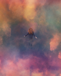 This is a vibrant and colourful portrait image of a woman floating in a sky of stars and rainbow coloured clouds. The woman figure is wearing black and has her back to the camera. She floats in the centre of the image and is quite small in relation to the size of the photograph. Around her are pink, orange, blue, aqua and yellow clouds. Her arms are outstretched to her sides, as though she was connecting to the scene around her or somehow magically propelling herself to float.