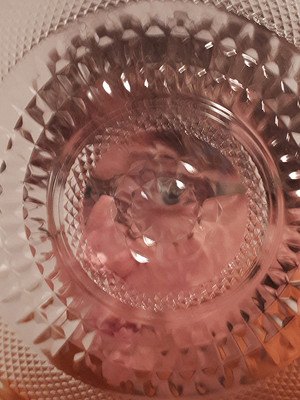 This is a colour portrait photo of a distorted face behind a circular patterned crystal glass bowl. The intricate design of the glass bowl refracts odd colours around the image in skin tones of pink and pale peach. Despite the odd effect, an eye can be recognised in the centre section of the bowl.