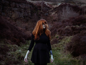 This is landscape image of a woman dressed in black who is stood in a dark and moody outdoors landscape. She has long ginger hair and her face is turned away from the camera. Over her eyes is a black piece of fabric, concealing part of her face. The landscape around her is a quarry that nature has reclaimed. There is heather in tones of dark purples growing around the green pathway she is stood on. Behind her there is a rocky outcrop with bare trees.