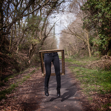 This square image depicts a pathway scene with bare tress in Winter on the left and right side with a tarmac grey path running from the centre out into the horizon. Stood in the centre of the photo is an ornate gold frame with a pair of legs wearing black jeans and boots protruding form it. The top half of the figure is invisible, as though he frame was some kind of portal with only the bottom half of the individual visible.