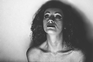 This is a landscape image of a woman who is shot from the lower shoulders upwards. The photo is in black and white and is highly contrasted so that the model's freckles and the contours of her face and neck stand out. She is looking upwards, away from the camera. The model is unusually lit from underneath her face, causing strange and unusual shadows to form around her face that is reminiscent of old black and white horror films.