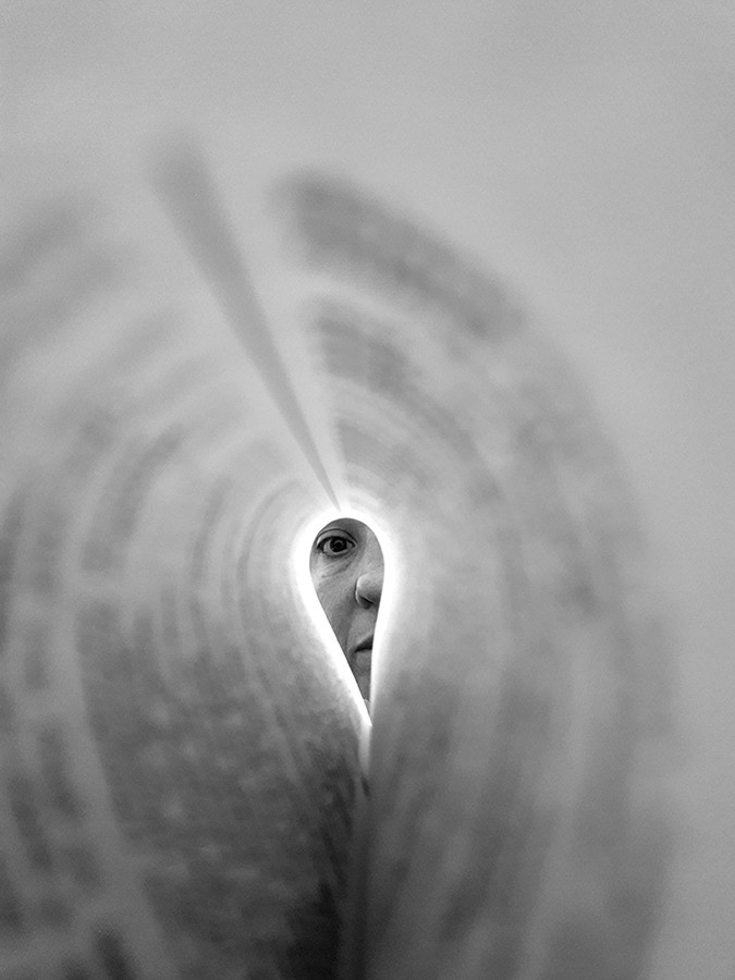 This is a portrait black and white photograph of a page in a book curled into an oval shape. The words of the page spiral around as the page curls and are blurred and unreadable. At the end of the page is a face looking down the length of the page in focus. An eye staring directly at the camera, part of a nose and lips are visible.