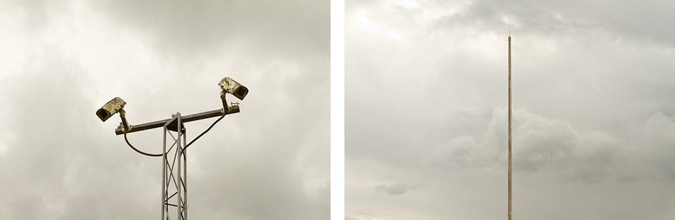 Left: Two CCTV cameras facing away from each other are set upon a pale grey metal tower with interconnecting poles that criss cross to form a secure structure. Behind is a grey cloudy sky. Right:  A tall empty flat pole stands amongst a grey cloudy sky.