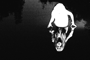 This is a black and white landscape image of a pool of water that covers the photograph. From the water, a ghostly figure appears from the waist upwards with two hands pressing against the water's edge. However the figure is made completely of white light in the image and it is only in the refection of the figure in the water that has an image of what she looks like. She has long black hair and is staring out directly tat the camera.