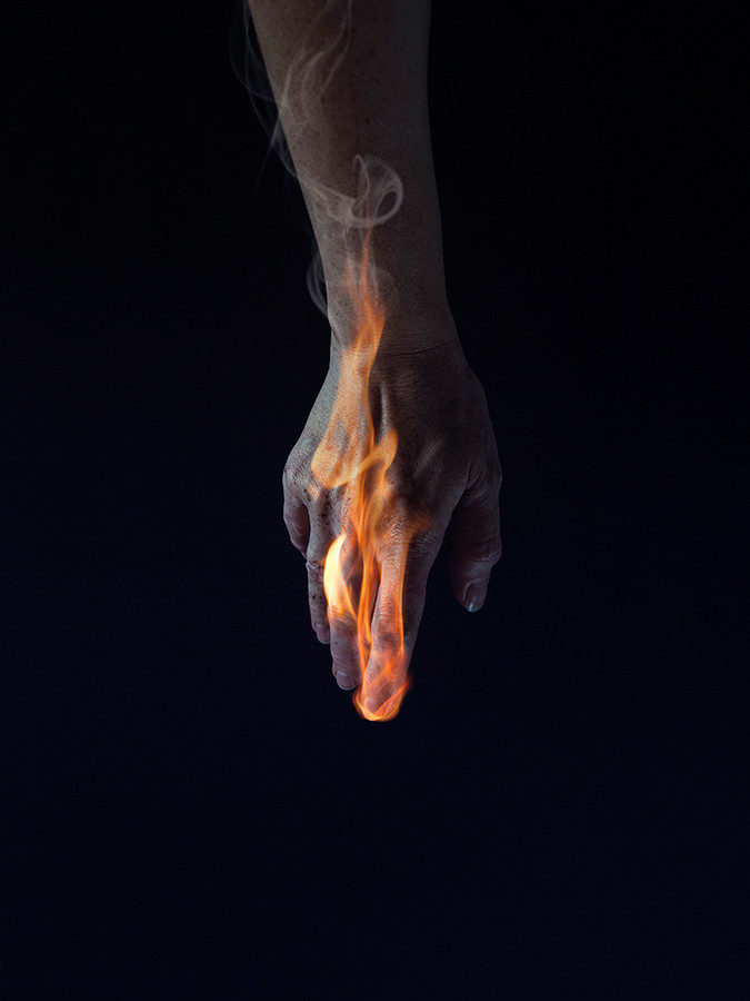 An arm hangs down in front of a black background. The hand is on fire with flames wrapping around it's fingers and rising up to the wrist. The arm and hand is an unnatural colour with a slight blue hue. Smoke rises from the flames upwards in the image.