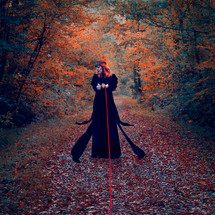 This is a square colour photograph. An autumnal scene is depicted, with trees coloured in tones of oranges and greens. A woman stands in a black floaty dress in the centre. Her head is turned to the side, away from the camera, perhaps in defiance. A singular red rope binds her hands together and leads towards the camera, as thought the viewer is the one that has trapped her. A crown adorns the model's ginger hair.