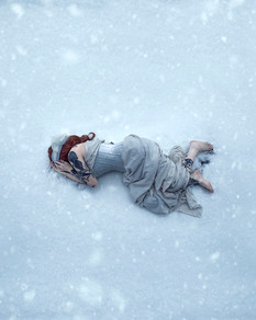 This is a colour portrait image of a woman in a white dress laying on an expanse of snow covered floor. Gentle snow flakes fall in the Wintery scene.  The woman's legs poke out from her skirt and bare arms protrude from the top of the dress. Her face is concealed by her hands which are drawn to her face. The body is posed in a loose foetal position. The snowy scene around her bares no footprints.