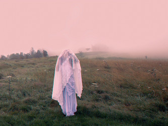 This is a colour landscape image of a woman wearing a white dress with layers of white fabric covering her face and arms. Through the fabric you can see the outlines of her arms as they are raised up towards her head. She stands in a field of mist that's an unusual colour of pinky red. The colours of the grass and trees in the distance are muted and faded in the fog.