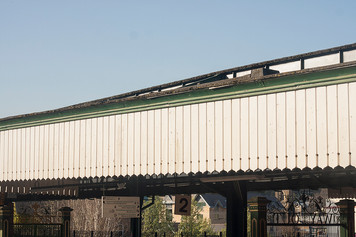 This is a photo of the roof of s train station. A pale blue sky presides over the top section of the image above the roof's edge. The roof is made from black coloured horizontal panels that is adorned with speckles of colourful lichen. beneath that are more horizontal cessions of green painted wood vertical panels of white wood which have pointed edges. A town with various buildings can be seen in the distance with signs to guide passengers from the platform.