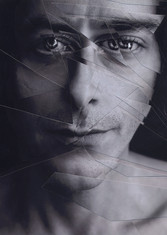 This is a black and white portrait photograph of a man's face. The image has been taken close to the model's face. He appears to be neutral in mood and is looking directly outward in a friendly manner. The image is distorted with layers of the photo cut up in small sections and placed slightly off to create a disjointed effect. The left side of the image is shadowy and shows the curves and facial features of the model.