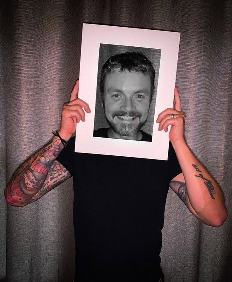 This is a colour portrait photograph of a man wearing a black t-shirt from the waist upwards. He is holding a large white frame to his face and smiling. The bright colours of his arm tattoos can be seen and contrast against the centre section of the white frame which has been desaturated into black and white. This effect is called colour popping and makes the image seem surreal and outside of everyday reality. Behind the man are grey long curtains.