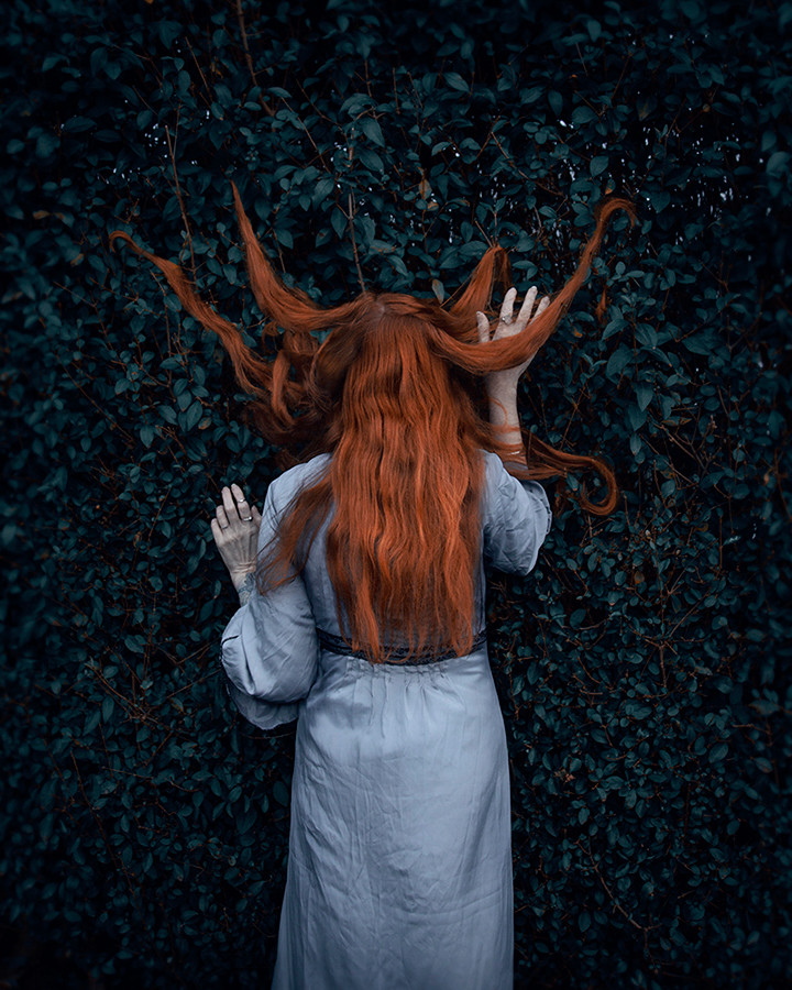 This is a colour portrait image of a woman with long ginger hair who is standing in the middle of the image with her back to the camera. In front of her is a tree in otherworldly tones of blue and green that fills up the entire photo. The woman appears to be embraced by the tree with it's leaves encroaching around her as long lengths of her hair are tangled in the branches.