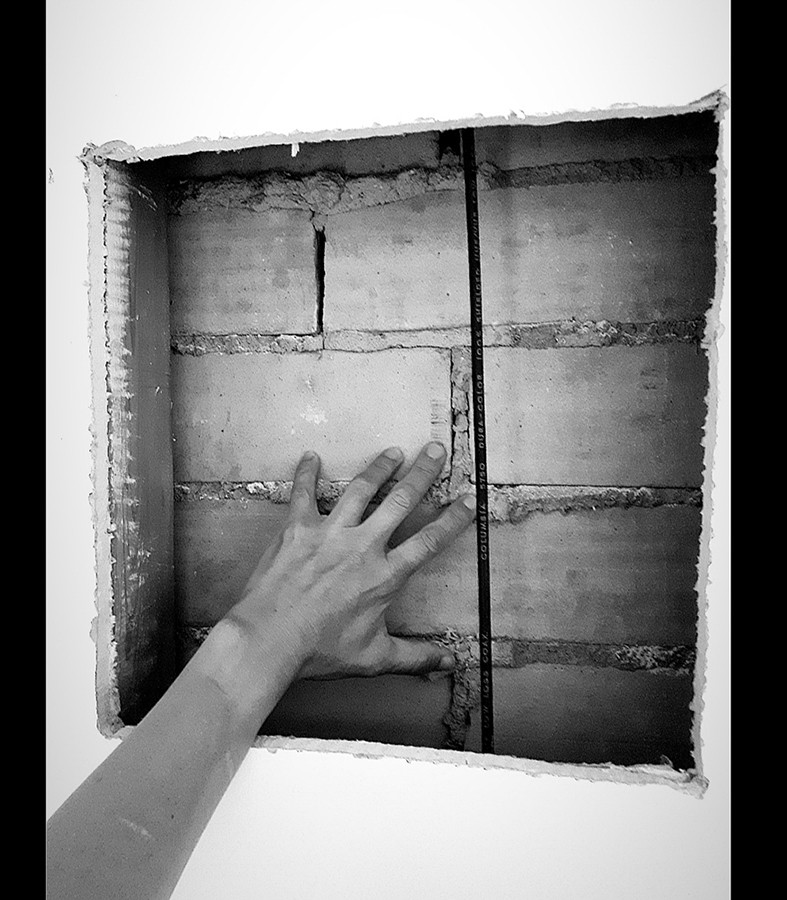 This is a black and white portrait image of a wall with a large square hole cut from it. Inside of this hole stands another bricked wall a few inches in. A hand is seen from the bottom left corner touching the bricked wall inside the hole. Two thin black strips of block colour frame the vertical sides of this photograph.