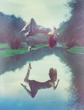 This portrait image seems magical and unearthly for the scene depicted within it. A lake can be seen, rising into the background with winter's bare trees on either side. A woman in a silver dress is levitating above with her back arched as if in ecstasy. The water beneath her reflects her mirrored image and show no clue as to how she is floating in midair. The image is toned in faded blue and orange tones.