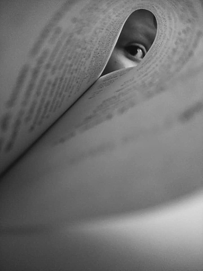 This is a portrait black and white photograph of a page in a book curled into an oval shape. The words of the page spiral around as the page curls and are blurred and unreadable. At the end of the page is a face looking down the length of the page in focus. An eye staring directly at the camera is visible, leaving the rest of the face as a mystery.
