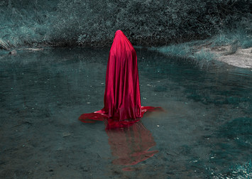 This is a colour landscape picture that is solely in two contrasting colour tones of blood red and turquoise blue. The image is of a cloaked bright red figure in a pool of water.  The small lake doesn't seem to be that deep judging from the tall length of the red figure, but never the less feels intimidating as the water could hold unknown depths. The cloak draped over the individual floats in the clear water and extends out in all directions around the figure. The figure's head is slightly tilted and it appears as though it is facing away from the camera and looking out to the scene beyond what is captured in the image. Grassy bankings and shrubs in turquoise blue tones frame the photograph on the top and right hand side. There is no indication of an explanation or motivation for why this figure is stood still in the water.  The red of it's cloaks links this particular photograph to two others from the exhibition.