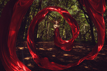 This is a landscape wide shot of a girl with auburn hair floating in the centre of the image in a forest scene. She is wearing a long red dress that flows downwards to the ground and then loops around the image twice in a circular pattern. Her arms are placed criss-cross style over her chest and her hair also appears to be floating. The forest scheme around her is in tones of green and dark brown for the floor. Beams of light fall through the canopy of trees and light the red fabric and girl.