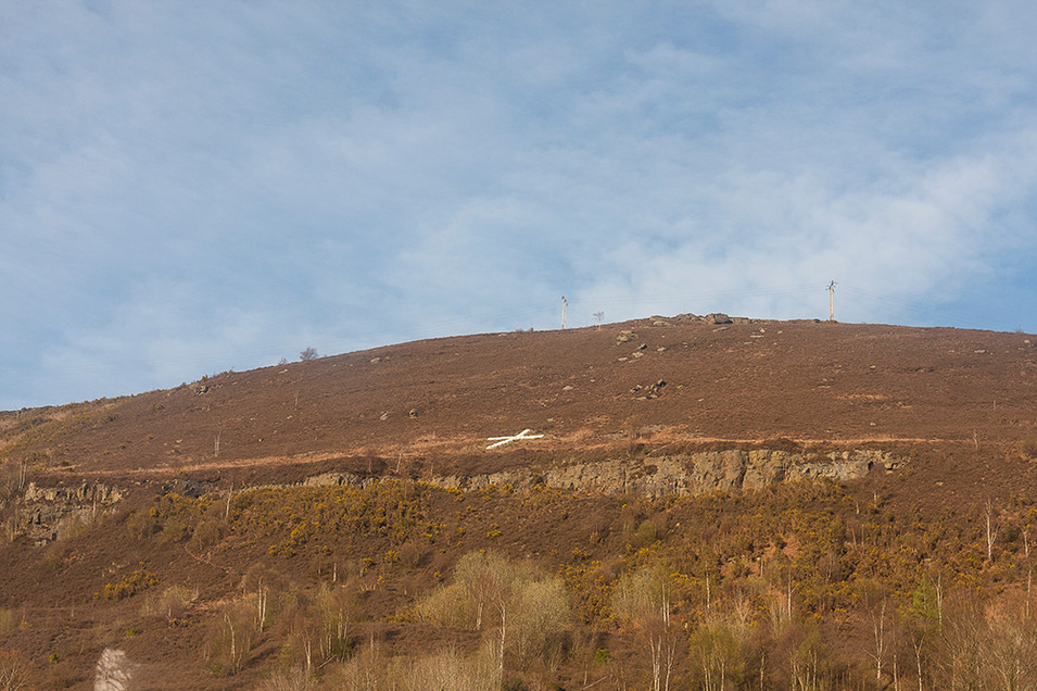 This is a photo of a mountain side coloured in tones of brown and red by dead ferns and trees. The thin trunks of silver berates form vertical lines in the image. A blue sky behind contrasts the colours of winter. A white cross made up of painted stones clings to the side of the mountainside in the centre of the image. The rumoured story behind this monument was that two local friends made a pact when they both went to war together that if one should perish, the other would build a cross in the landscape above where they grew up as a tribute to their sacrifice.