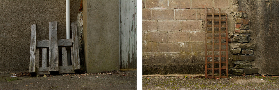 Left: This is a photograph of a broken wooden pallet leaning against an external grey wall. A white drain pipe rises from behind the pallet. To the right there is a wooden door with white paint peeling away and exposing dark brown wood. Right: This is a picture of another piece of wood against an external wall, this time part of a fence. The wall is made from breeze blocks with a sight pinky tint. These meet a more traditional stone section of wall that protrudes outwards. Another concrete section is on the other side of this.