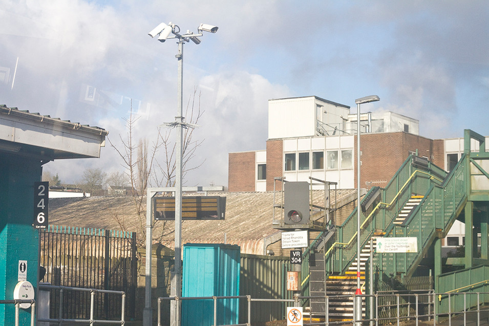 This train station scene appears busy from the multi layers buildings, signs, poles and lamp posts but doesn't feature any people in the shot. There is a green staircase, where it leads is unknown. Secretary CCTV cameras are pointed in every direction and tower above the scene on a tall silver post just off centre to the left side of the image. Clouds are forming in the background behind.