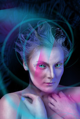 This is a colourful portrait image of a woman with special effects make-up on to look like an alien of some sort. She is wearing contact lenses which distort the colour of her eyes to an unusual light green. Her blue hair is raised in sculptural waves from front to back. This photo is from her chest upwards and incorporates her hands which are gently placed near her neck. Peculiar lights illuminate and change the tone of sections of the image to bold pinks and pale aqua blues. Some lights swirl around her head, drawing attention to her face.