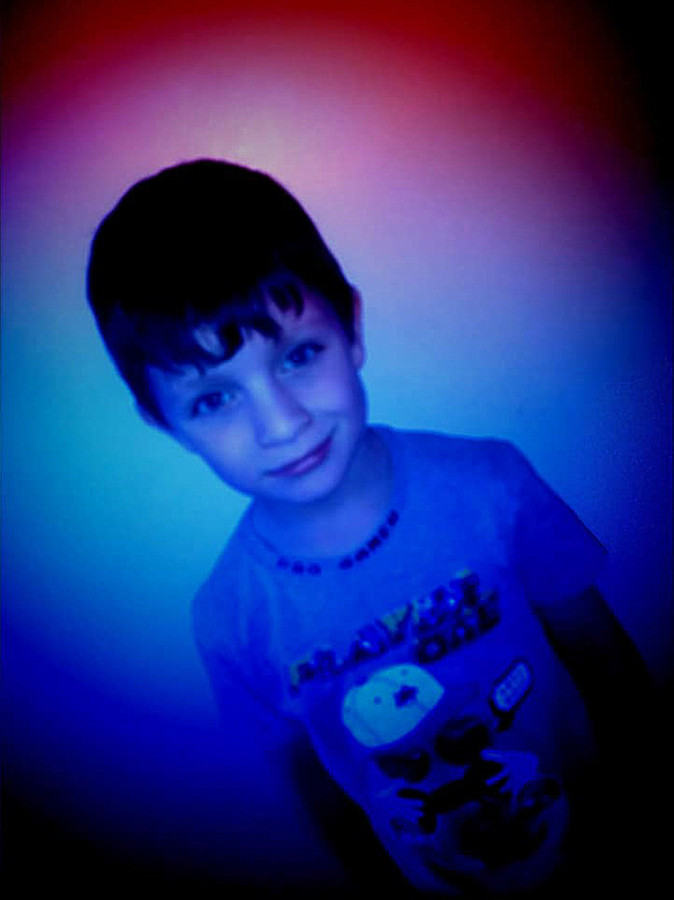 This is a colourful portrait image of a young boy from the wait up in tones of red and blue. The boy is stood looking directly at the camera and the image has been taken on an angle so that he is slightly diagonal in the picture. The top section of the photograph is patched in ares light and the bottom in bold blue light.