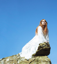 This portrait image is cropped as a square like shape, much like a music CD or record cover. The photo is of a woman sat on a rocky ledge of a cliff. She is looking outward into the distance and not at the camera. She is wearing a white floaty victorian styled dress. A cloudless blue sky contrasts with the flowing red hair of the model. The image has a slightly green hue to it, much like the vintage record covers that are colour degraded by age.