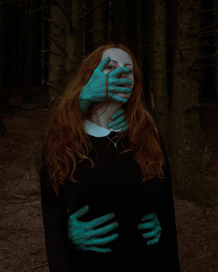 This is a moody portrait photograph of a woman with long ginger hair stood in a dark forest. Four creepy looking greeny-blue hands appear from around the back of the woman and are grabbing at her face, partially covering it. The woman's eyes are visible and she is looking directly into the camera. The other set of hands grab at her waist, holding her in place.