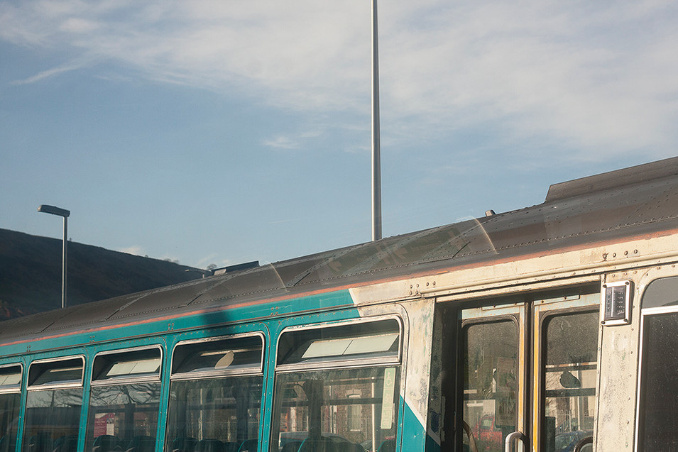 This is a photograph of the top of another train carriage. The carriage is bathed in golden sunlight which highlights the textured dirt and grime that covers the white and turquoise paintwork. In the distance is a dark and steep mountainside. Just off centre, a tall silver pole cuts the image in half.