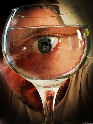 This is a colour portrait image of a wine glass filled with water. Behind the glass is a man's face. The glass distorts the man's face so that his eye appears to be much larger than the rest of his facial features. The image has warm tones and is dark around the edges to draw the eye into the middle of the image.