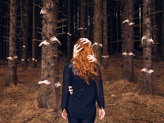 This is a colour landscape format photograph of a woman with long wavy ginger hair stood in the centre of a forest. Her back is to the camera as she stands at the edge of a line of trees. Around her head and waist are hands that seem to be pulling her into the forest. The surrounding trees also have hands emerging from them and grabbing the trees.