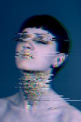 This is a close up colour portrait of a woman from the shoulders upwards with black tied back hair and pale skin. Her eyes are closed and her lids are painted with dark make-up. Her lips and neck are decorated with small flecks of gold leaf. Behind there is a dark blue background. The image is a 3D glitch effect. A glitch effect is a digital aesthetic made of flaws and distortion where sections of the image are repeated and in odd colour tones.