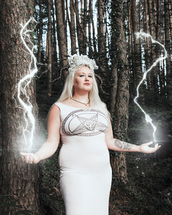 This is a portrait colour photograph of a most wonderful magical human wearing all white in a dark and mysterious looking forest. The model has long white blonde straight hair and is wearing a long white dress. On their head is a white headpiece made of white flowers and pearls. Two black horns protrude from the model's head.  The model's hands are both raised at their sides and magical white lightening sparks up above their head in the scene.