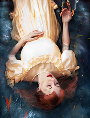 This is a colour portrait image of a ginger haired girl with red lips wearing a victorian inspired pale yellow dress. She is half submerged in blue coloured water. Her head down to her knees are visible in the shot. Brightly coloured leaves in tones of red and orange float in the water around her. The women is raising her right hand upwards out of the water and flames can be seen on her fingertips. She appears to be at peace with her eyes closed.