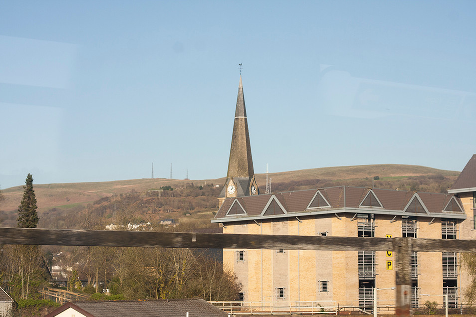 This is a photo in Winter with bare leafless trees scattered around the scene of buildings that fade into mountains and blue sky. In the foreground is a long length of wooden fence, signifying a barrier between the experience of the interior of the outside world which is briefly seen through the windows of the train carriage. A large pale orange NCP car park building stands in the right section of the image. A tall church steeple pierces the space behind and beyond that a brown mount aide with three metal masts can be seen.