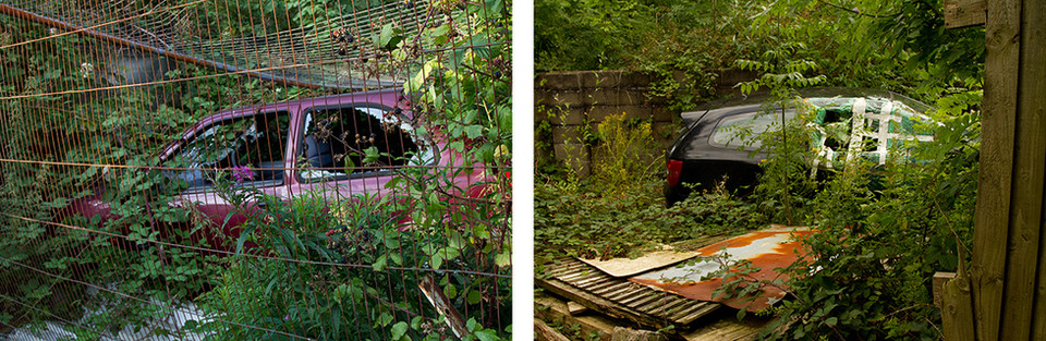 Left: A broken ares car with smashed windows lays behind a rusted metal gate. Brambles and shrubs grow over the car, almost concealing it from the viewer. Right: This is an image of another broken car with a smashed window. Nature is also reclaiming the scene and brambles have been left to grow wild. The broken window has sticky tape over it, as though at some point there was an attempt to fix the car. Panels of rusted metal lay at the side of the car.