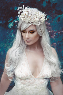 This is a colour portrait of a woman dresses all in white with white hair to match. She is sat in amongst a clearing of brambles and trees, all of which are coloured in a very unnatural blue tone. On the woman's hear sits a white crown of flowers. She is looking downwards, as if sad.