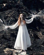 This is a portrait image of a woman stood in a burnt landscape of charcoaled grass and shrubs. The woman is wearing a floaty long white dress and has has long ginger dreadlocks and pale skin. She is stood, bare footed upon a rock. Her arms are raised in the air with what appears to be broken glass fragments around them. The shattered glass is both behind her one hand and in front of the other, suggesting that she is trapped in a glass box that we cannot see except for the broken areas.