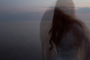 This is a landscape image of a sea scape at dusk, just after the sun has set and darkness has creeped into the scene. A girl with long dark hair is stood in waist high water with her head down towards the sea around her. She appears to be blurred through motion or perhaps due to a double exposure where two images are combined. It could be interpreted as her aura seeping from her body to create this other ghostly like figure next to her.