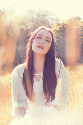 This is a bright and colourful portrait image shot in summer with golden yellow and subtle pink tones. A woman wearing a white dress with pale skin, red lips and long brown hair is sat in a field of tall sunlit grass. Behind her are tall trees. The sun gentle catches the side of her hair and illuminates the golden tones within it. She appears to be calm and relaxed and is looking away from the camera and slightly upwards as if daydreaming.
