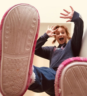 This is a colour image of a woman standing above the camera looking downwards with an amusing and fun facial expression. The perspective of the photo is from the ground looking upwards. Two feet wearing fluffy slippers hover above the camera phone. The woman's hands are open and in the air, as if she was expressing a surprised look.