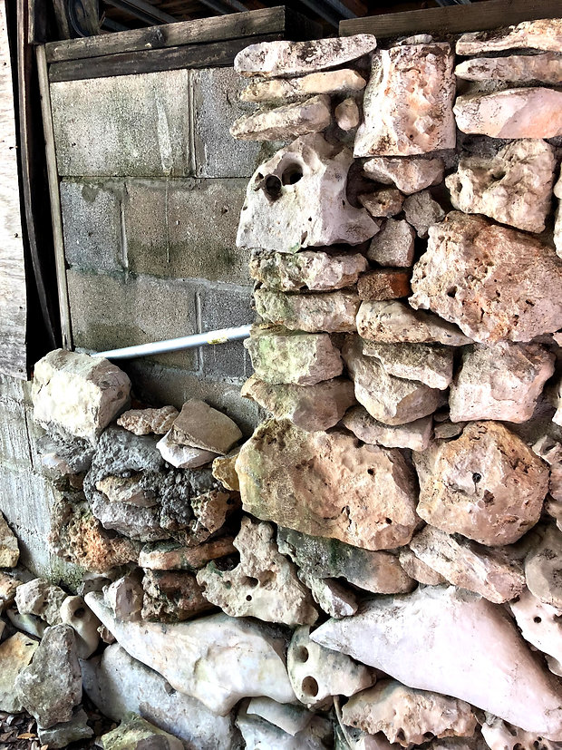 Rock wall built by dementia. The left side is haphazard with goopy mortar but the right is beautiful with honeycomb rocks stacked in aesthetic order with rocks hand picked from Hudson Bend near Lake Travis (Austin, TX).