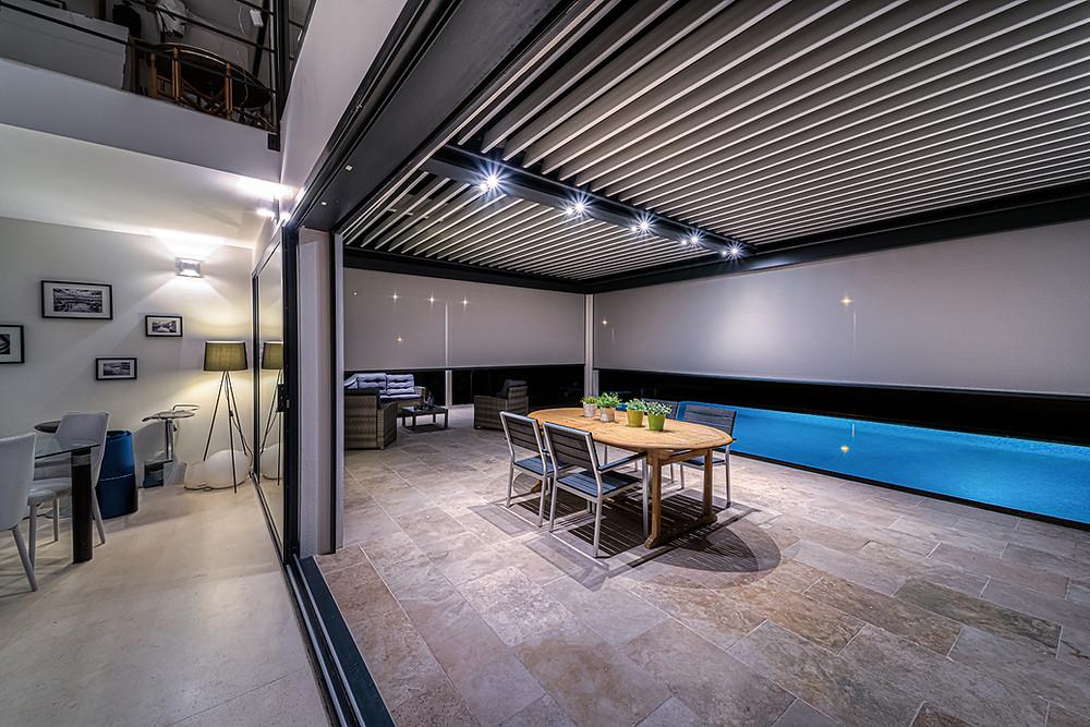 Pergola bioclimatique Sol Design Solembra gris anthracite aux lignes architecturales et élégantes avec 2 arches blanches suppression de poteau par haubanage éclairages LED et stores Zip Screen vue de l'intérieur de la maison