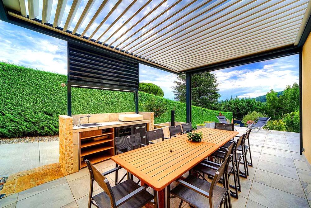 Pergola bioclimatique sur-mesure Solembra avec lames orientables poteau décalé pour protéger terrasse et cuisine d'été vue de dessous