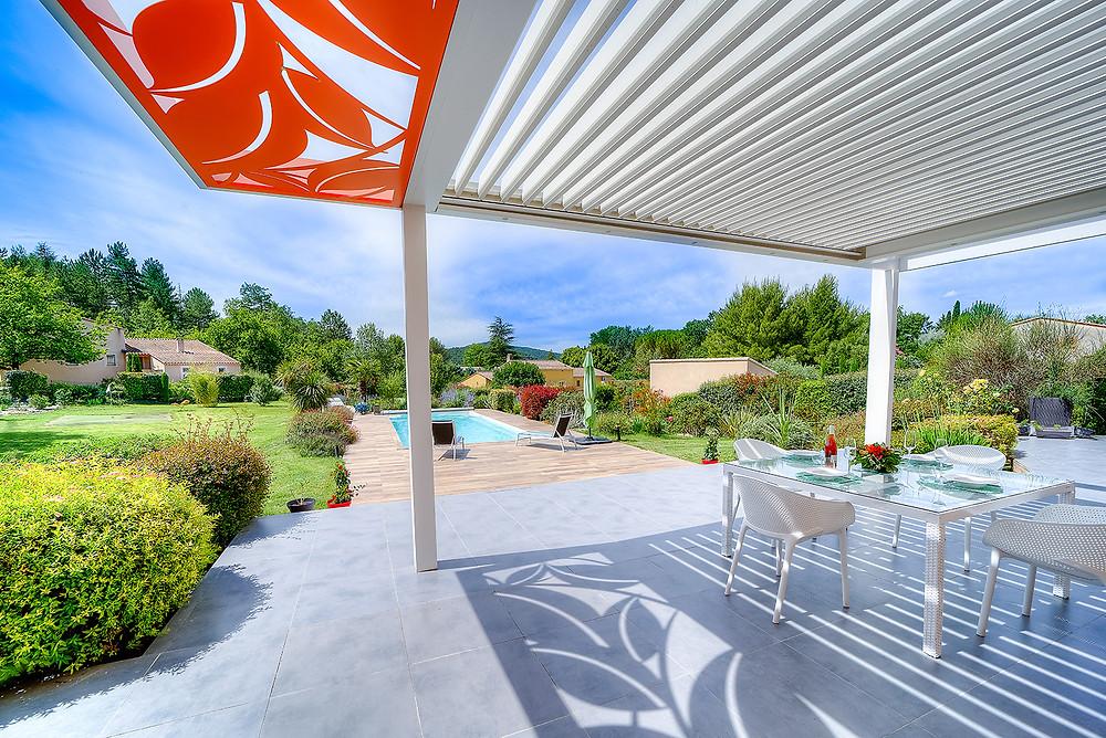 Pergola bioclimatique blanche sur-mesure Sol Design Solembra avec lames orientables et accessoires haut-de-gamme claustra décoratifs orange vertical et jeux d'ombres et de lumières au sol vue de dessous