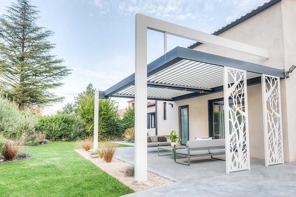 Pergola Bioclimatique Solembra Sol Design haut-de-gamme gris anthracite et blanche avec arche suspendue, claustras décoratifs et spots LED orientables