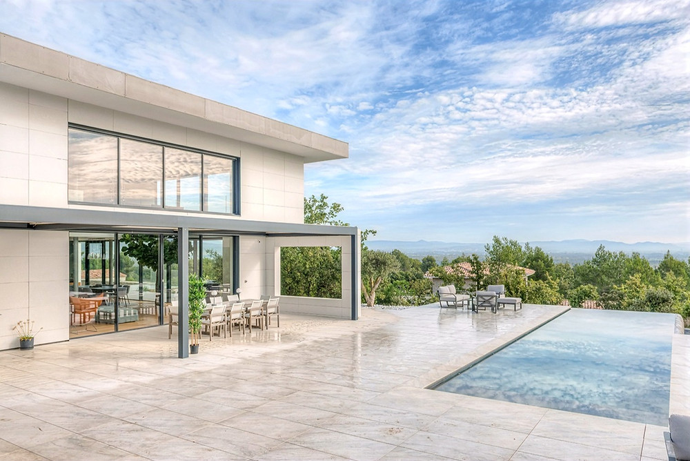 Pergola bioclimatique Sol Design Solembra avec portée XXL poteau décalé pour une ouverture de vue optimale depuis la baie vitrée et intégration sur-mesure à l'architecture existante de cette maison contemporaine