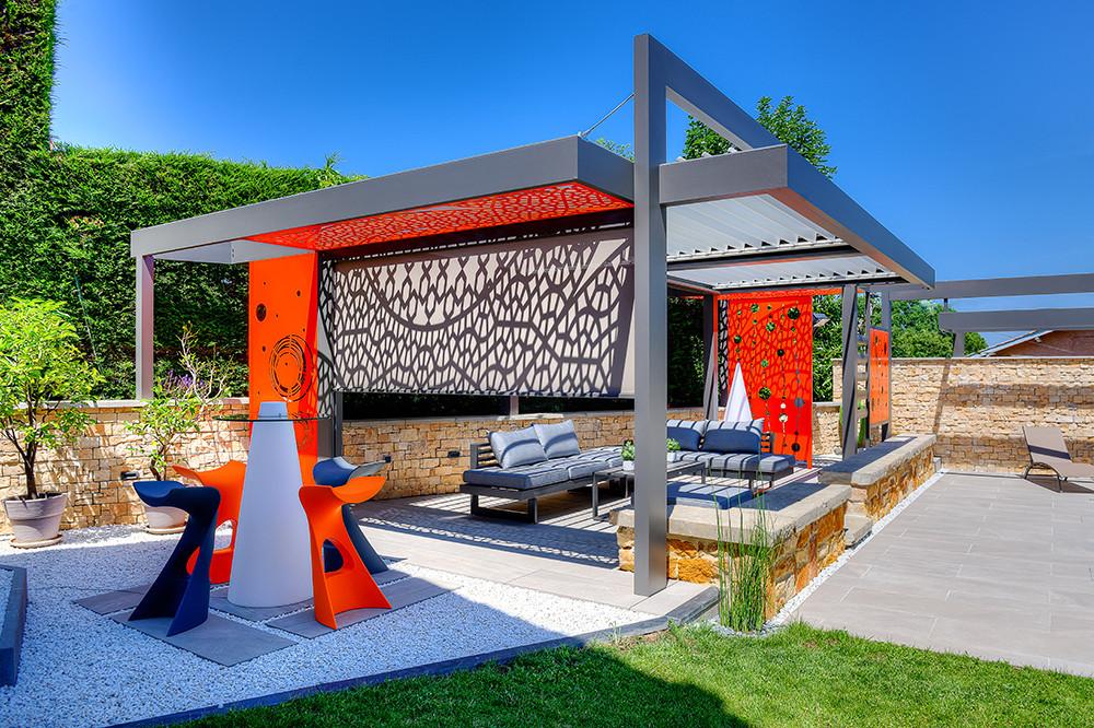 Pergola bioclimatique autoportée grise sur-mesure Sol Design Solembra avec 2 modules de lames orientables et arches et accessoires haut-de-gamme claustra décoratifs orange vertical et horizontaux différents motifs et jeux d'ombres et de lumières sur le store zip screen latéral
