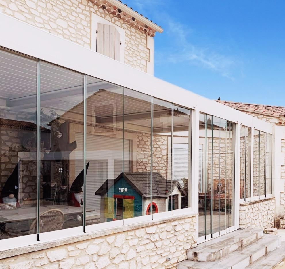 Photo de la pergola bioclimatique sur-mesure avec vitrage Sol Design Solembra sur une maison en pierre rénovée par nos clients à Arles, Bouches-du-Rhône, dans le Sud de la France, comme nouvelle pièce de vie en toutes saisons - vue de côté